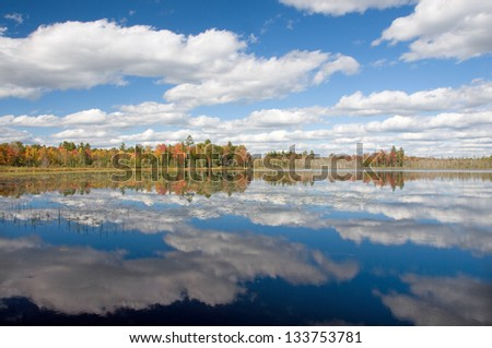 Photograph of an awesome autumn sky beautifully reflected in the waters of a remote northwoods lake in Wisconsin. - stock photo