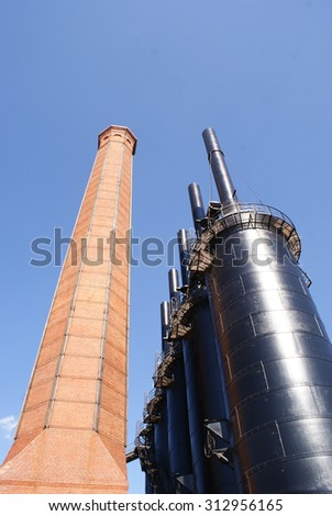 Photograph of an industrial metal structure and a brick tower