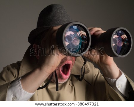 Photograph of an NSA agent in trench coat and hat looking through binoculars. The agent is shocked to see an FBI agent watching him. - stock photo