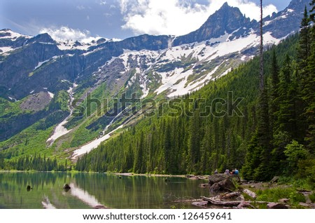 Photograph of beautiful Avalanche Lake high in the mountains of Glacier National Park being enjoyed by a group of day hikers. - stock photo