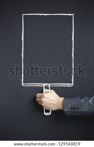 Photograph of Business mans holding a sketch of an empty white sign. - stock photo