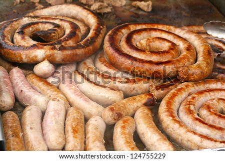 Photograph of fresh Italian sausage being grilled outdoors for carnival food menu, also known as fair food or street food. - stock photo