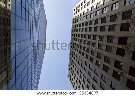 Photograph of office buildings with clouds reflecting off the windows - stock photo