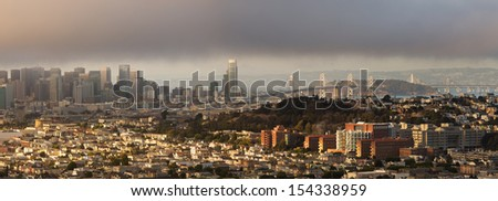 Photograph of San Francisco, including downtown skyline and the Bay Bridge, on foggy sunset.  Taken from Bernal Heights Park. - stock photo