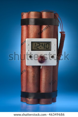 Photograph of sticks of dynamite with a timer on a blue background - stock photo