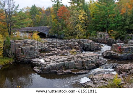 Photograph of the Dells of the Eau Claire, a spectacular series of small waterfalls between the rocks of a natural rock garden located in northern Wisconsin.  Shot during the beauty of autumn. - stock photo