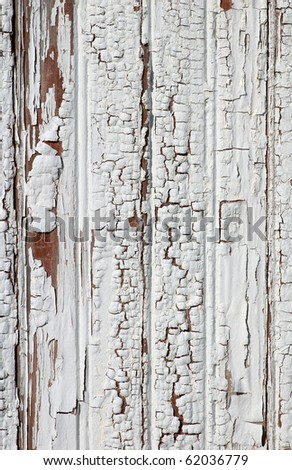 Photograph of the interesting peeling, bubbling and worn wooden side of a white storage structure in an old farming community.  Could be used as a texture or background. - stock photo