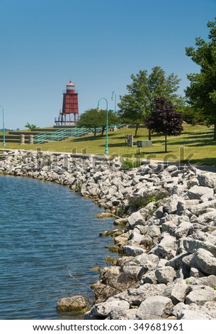 Photograph of the picturesque harbor front of a Wisconsin, Lake Michigan harbor with a lighthouse as a backdrop. - stock photo