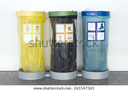 Photograph of three trash cans, each color to recycle different kinds of garbage. - stock photo