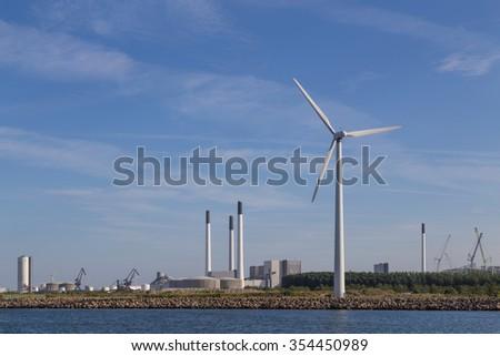 Photograph of wind power plants and industrial buildings in Copenhagen, Denmark. - stock photo