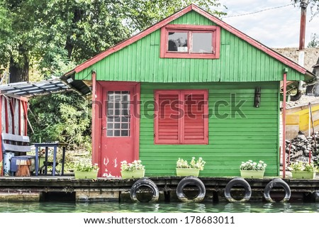 Photograph represents an old, handmade wooden green-red painted hut, placed among many, side by side, along the Sava river banks, Belgrade - Republic of Serbia. - stock photo
