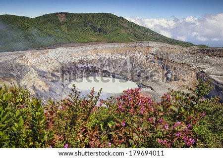 Photograph showing the main crater of the Poas Volcano in Costa Rica surrounded by colorful vegetation. - stock photo