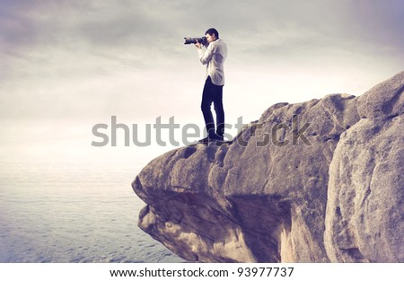 Photograph taking pictures from a rock over the sea - stock photo