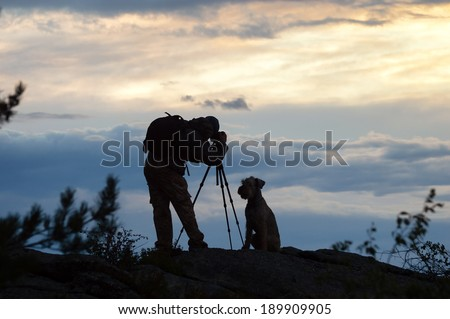 Photographer and dog silhouettes in the mountains at sunset  - stock photo