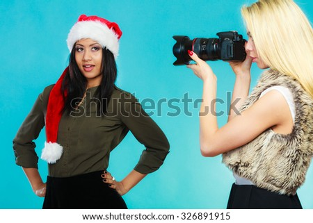 Photographer and model. Caucasian blonde girl shooting images, taking photos with camera., photographing african woman in santa helper hat. - stock photo