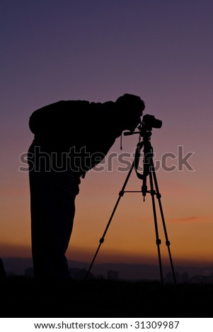 Photographer and sunset - stock photo