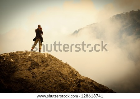 Photographer at the work in the mountains - stock photo