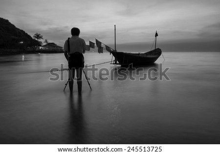 Photographer  Boats at the beach during sunset black and white tone.  - stock photo