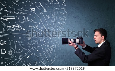 Photographer boy shooting images while energetic hand drawn lines and doodles come out of the camera - stock photo