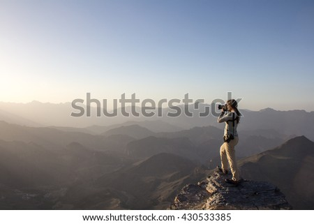 Photographer capturing the landscape of Oman mountains at sunset.