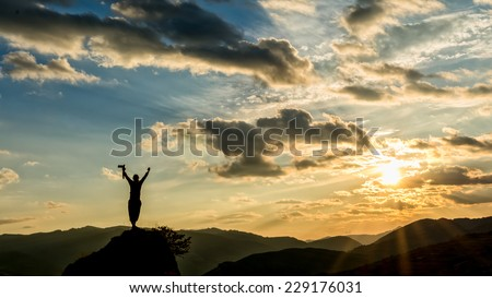 photographer celebrating success on from the peak of a cliff in a beautiful sunset