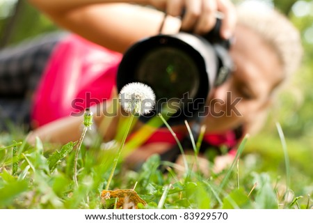 photographer, female  photograph with camera taking a macro  picture of flower - stock photo