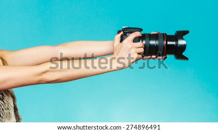 Photographer girl shooting images. woman hands holding camera taking photos. Vivid blue background