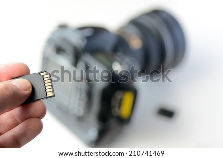 Photographer hand holds Memory card - Flash card against professional DSLR camera in the background.Concept photo of photographer , photography, lifestyle.  copy space. - stock photo