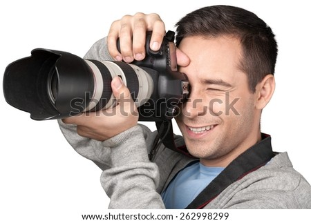 Photographer. Happy young man clicking photo from camera - stock photo