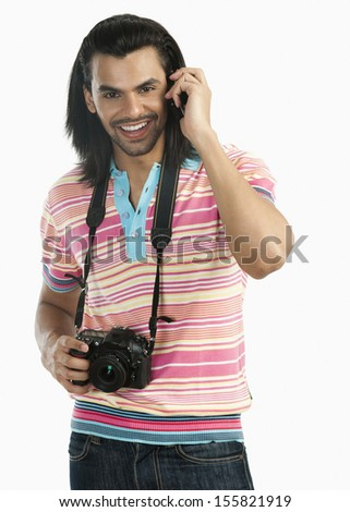 Photographer holding a digital camera and talking on a mobile phone - stock photo