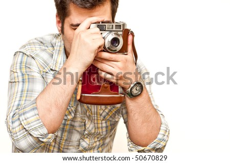 Photographer holding a vintage camera isolated on white - stock photo