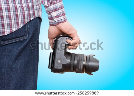 Photographer holding camera near the legs on blue gradient background -In this photo the logos, brand, or anything that can bring to a particular object has been deleted to be 100% commercial. - stock photo