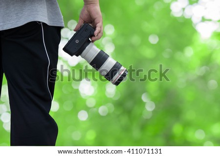 photographer holding camera with green background