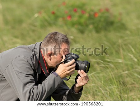 Photographer in action, flower shooting on meadow - stock photo