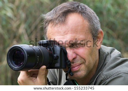 Photographer in action in forest - stock photo