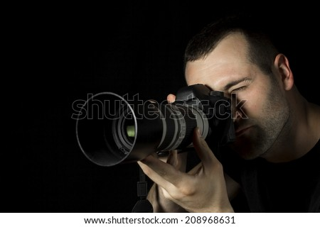 Photographer in action on a black background. Low key - stock photo