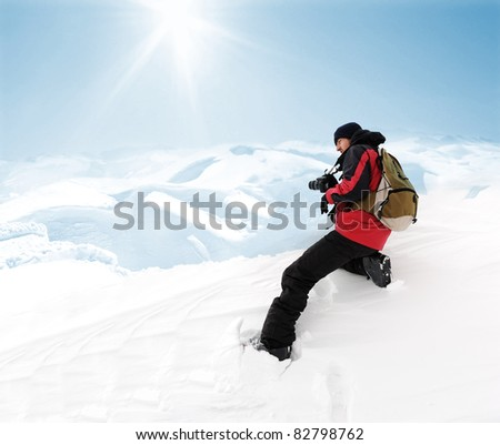 Photographer in extreme conditions getting picture of beauty mountain view - stock photo
