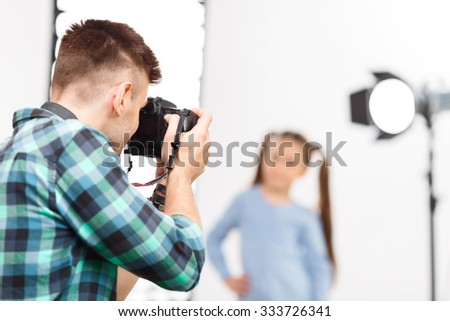 Photographer in motion. Young handsome photographer upholds his camera while shooting. - stock photo