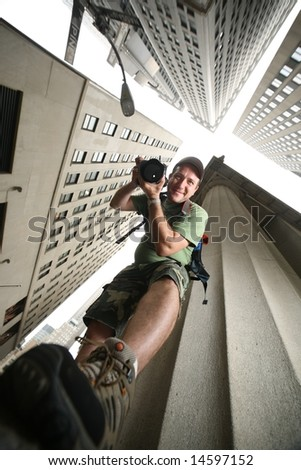 Photographer in New York City. Wide angle view from below. - stock photo