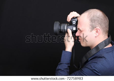 Photographer in profile, holding a camera - stock photo