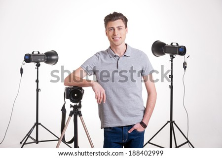 Photographer in studio. Handsome young man in polo shirt leaning at the tripod with camera while standing in studio with lighting equipment on background  - stock photo