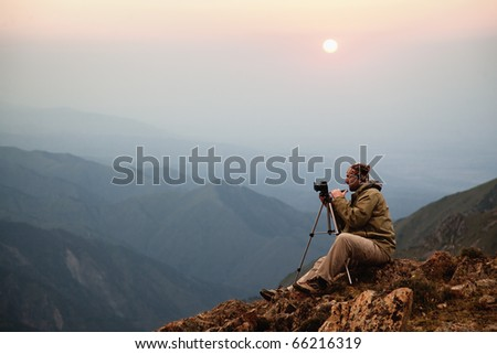 Photographer in the mountains at sunset - stock photo