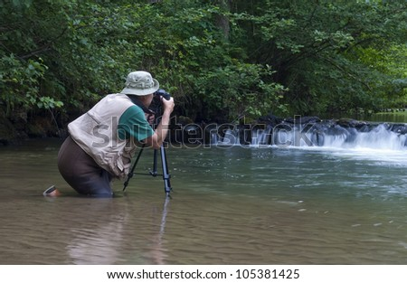 photographer kneeling in a stream next to a small waterfall - stock photo