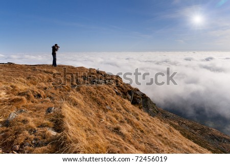 Photographer makes the photo above the clouds in the mountains - stock photo