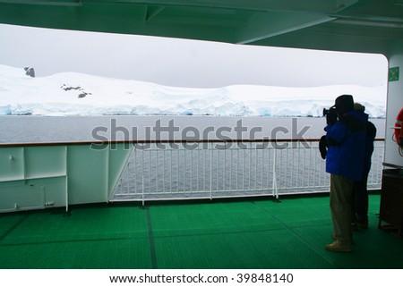 Photographer on cruise ship, and glaciersErreras Channel, Antarctica - stock photo