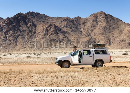 photographer on safari in Africa on his car - stock photo