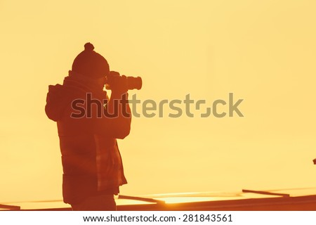 Photographer on the building roof, shooting the morning scenery. - stock photo