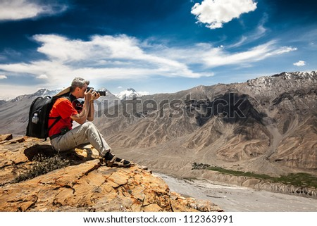 Photographer on the high mountain does its job. - stock photo
