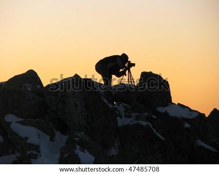Photographer on top in sunrise - stock photo