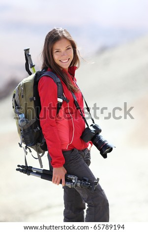 Photographer outdoors in nature taking pictures during hiking trip on Teide, Tenerife, Canary Islands. Beautiful smiling Asian / Caucasian woman. - stock photo